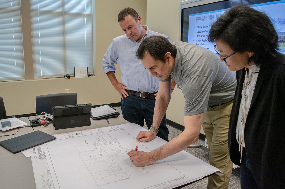 3 people collaborating over blue print